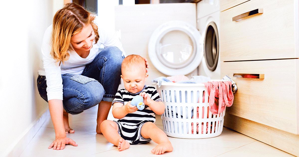A mom with her baby and a laundry hamper
