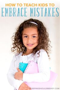 How to Teach Kids to Make Mistakes: A smiling little girl holding notebooks