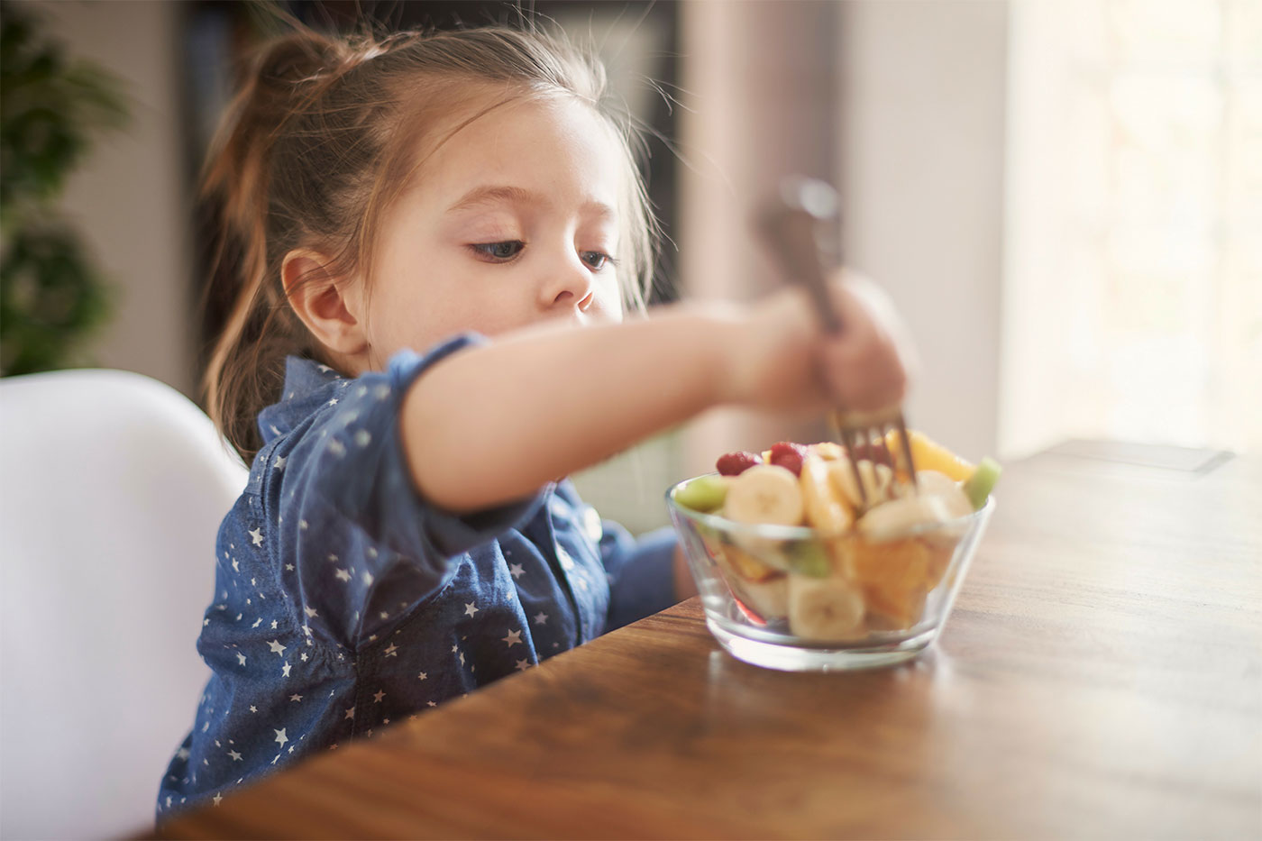Little girl eating a snack of fruits