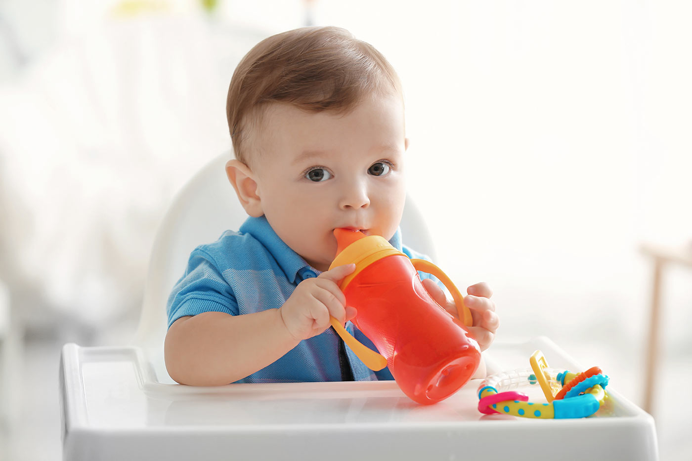 Baby drinking a sippy cup in a high chair