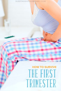 Pregnant woman in the first trimester, sitting on her bed, clutching her tummy from morning sickness