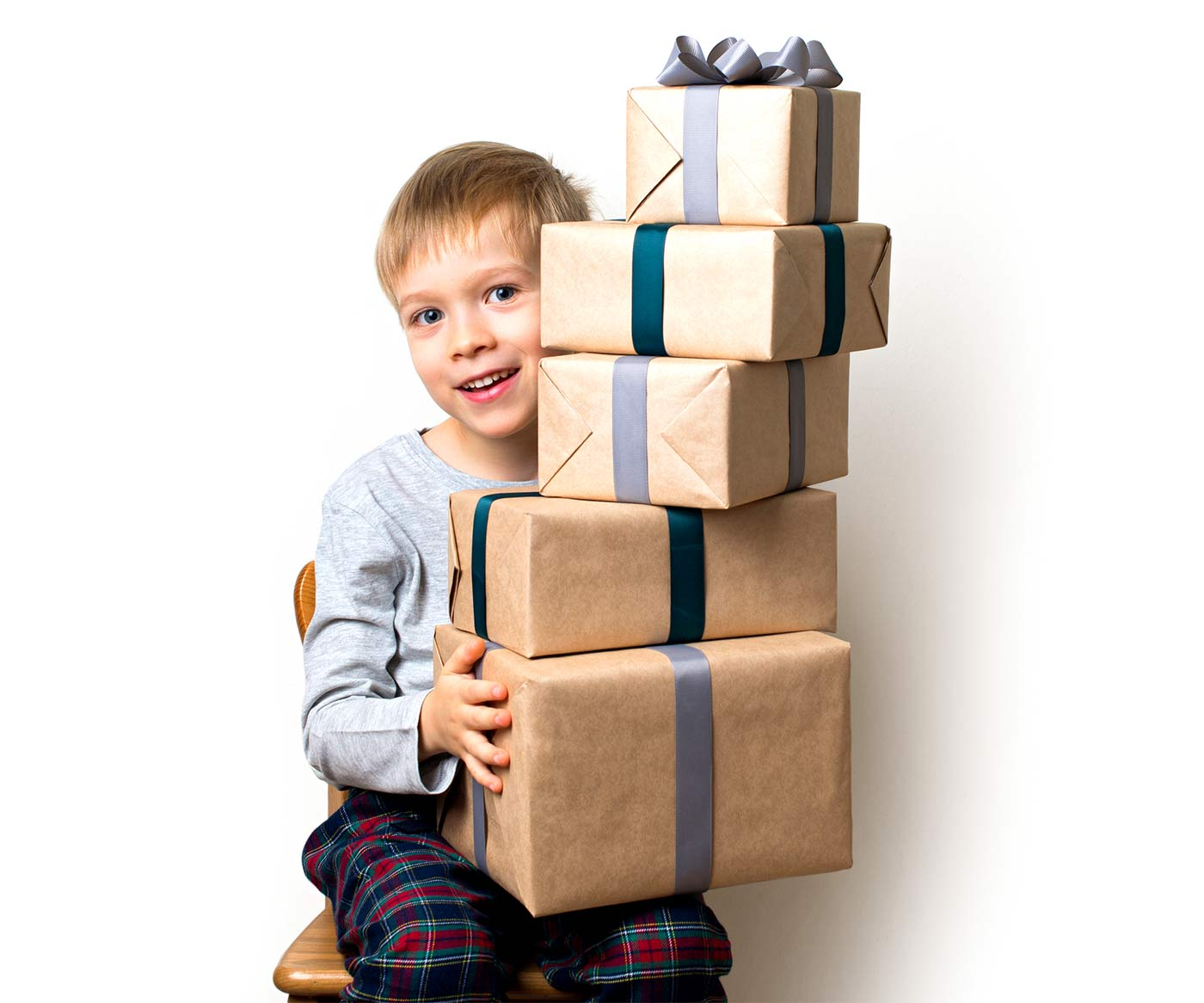 Grandparents spoiling grandchildren, a boy sitting on a chair with a pile of gifts