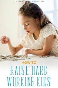Hard working kids: little girl playing puzzles at home