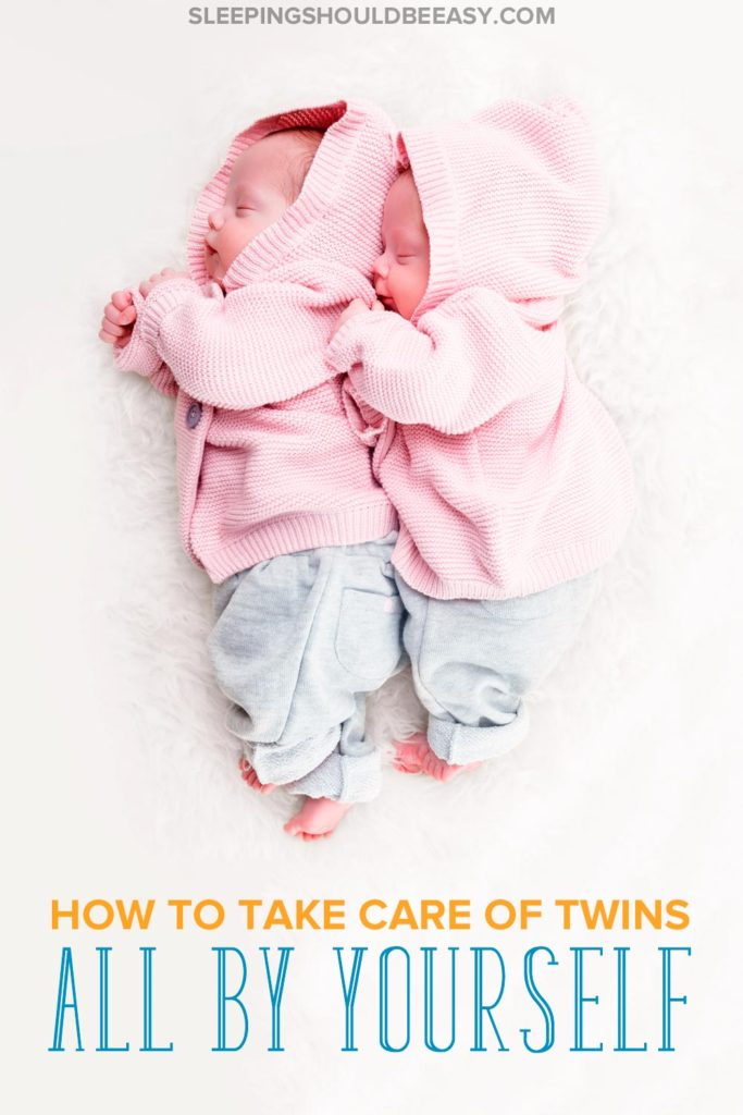 How to take care of twins all by yourself: Twin babies in pink sweaters sleeping
