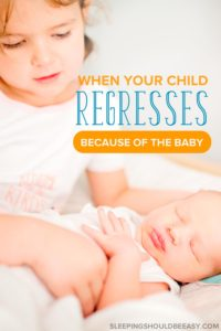 Little girl looking at her new baby sibling: When your child regresses because of the baby