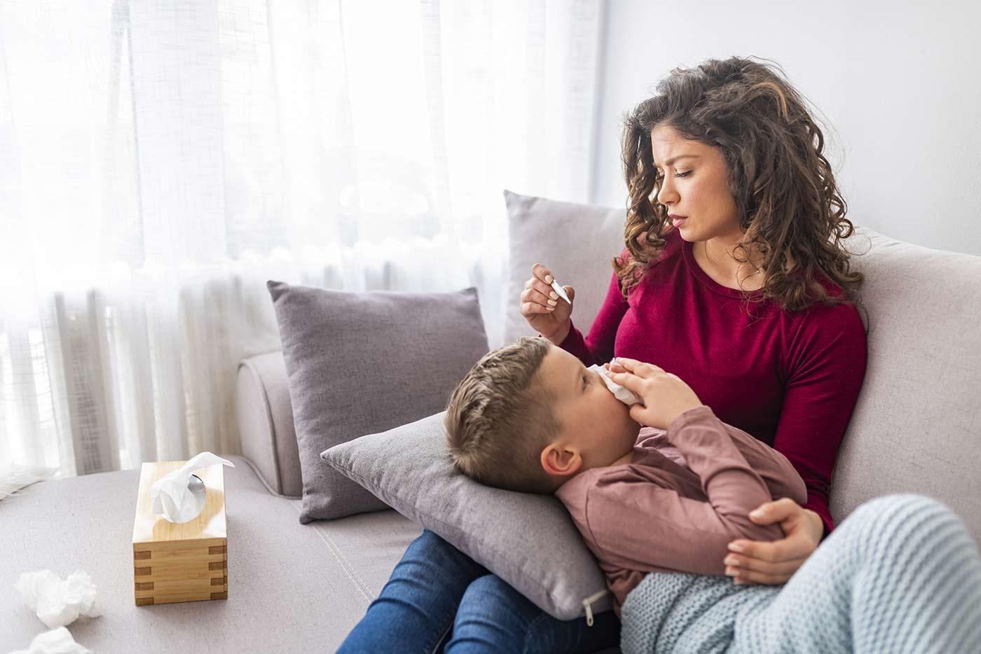 Mom taking son's temperature