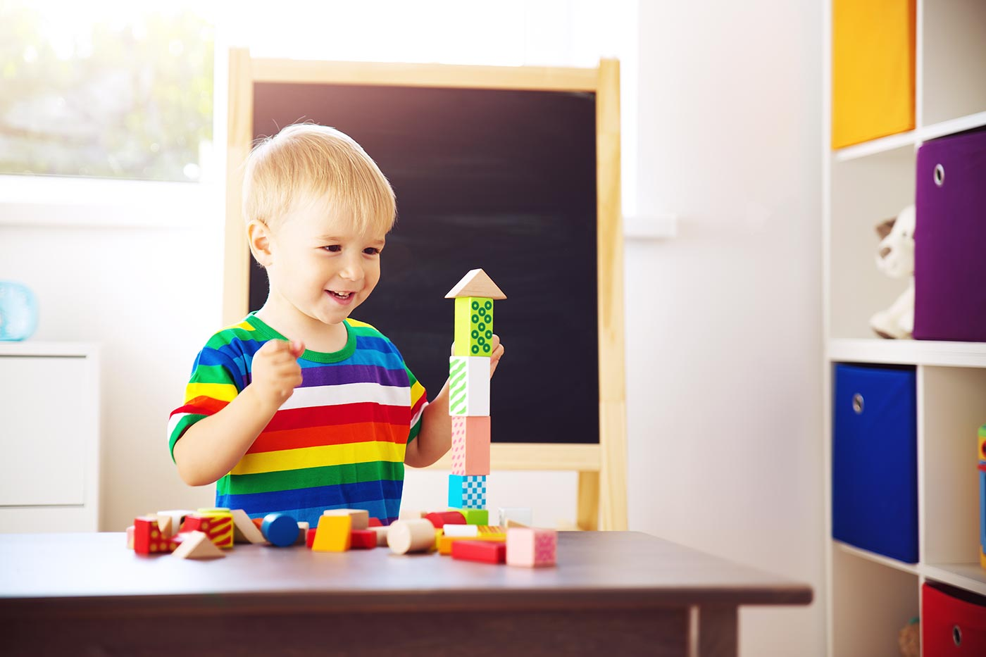 Little boy proud of building a tower of bricks