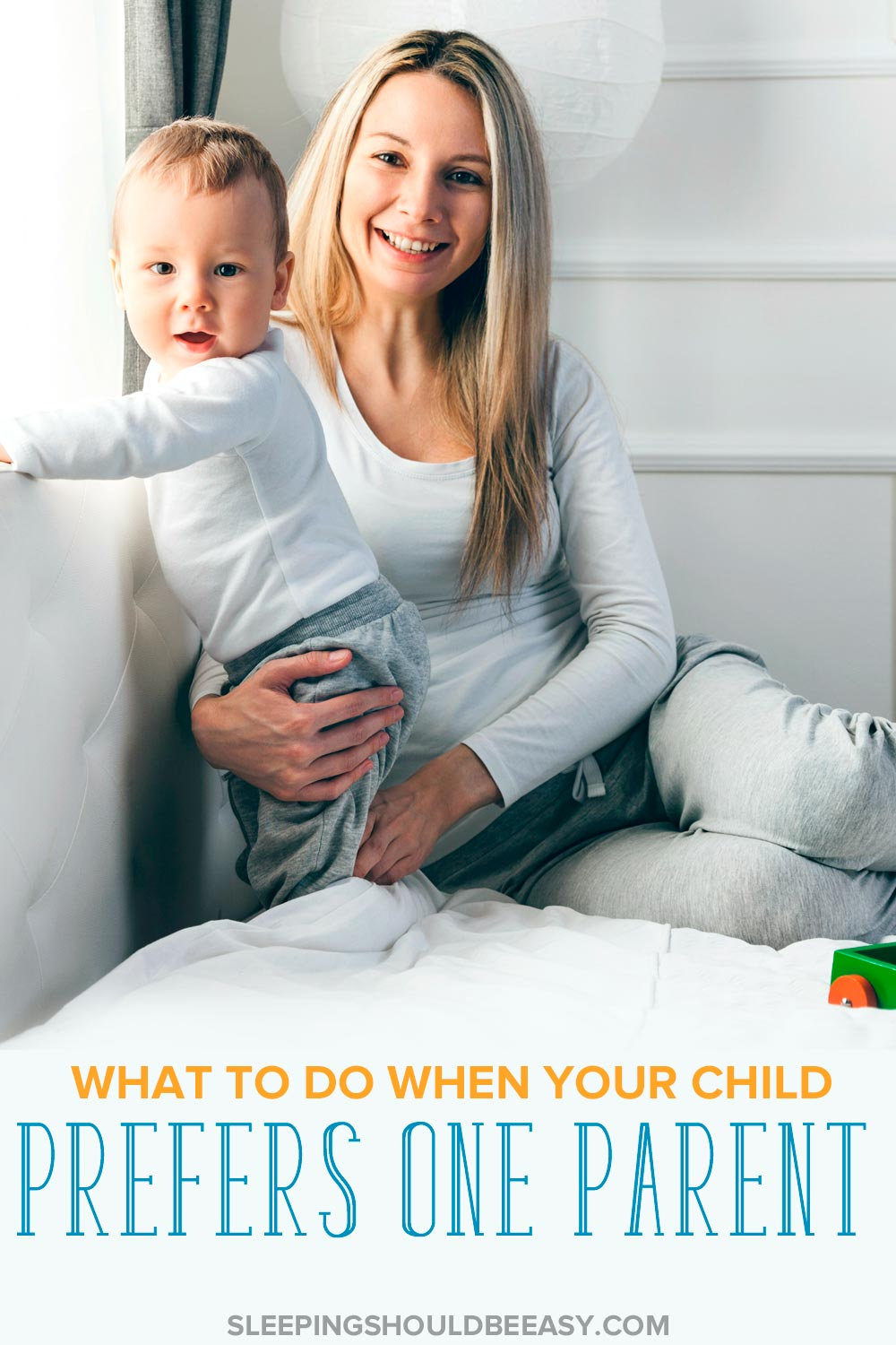 Parent sitting on a bed with a toddler, peering over the rail