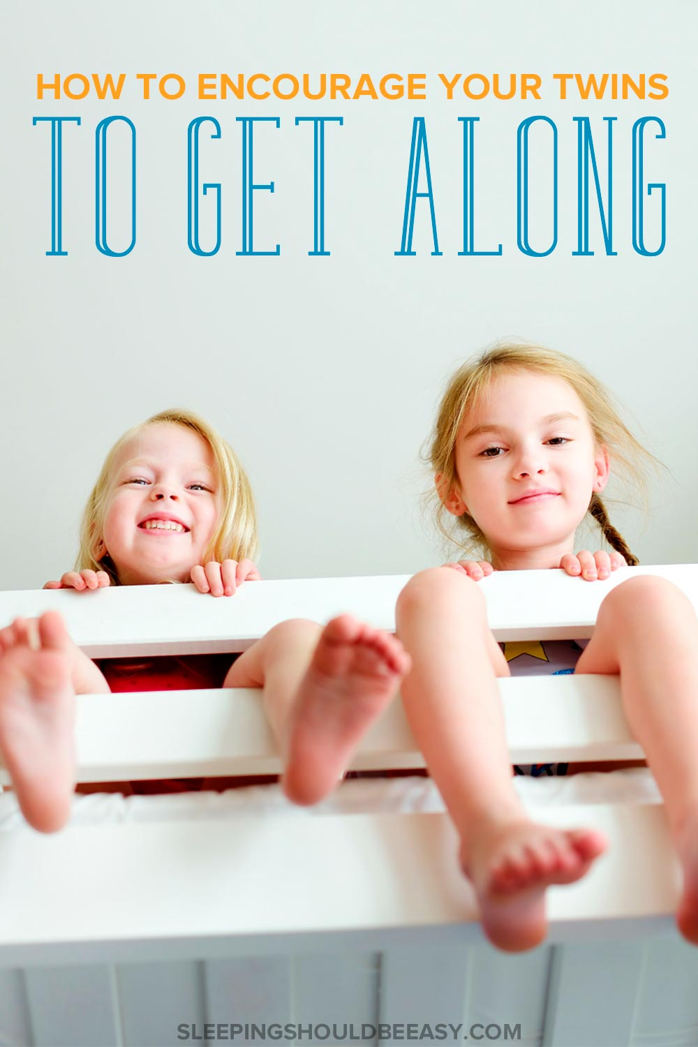 Twin girls sitting on a bunk bed