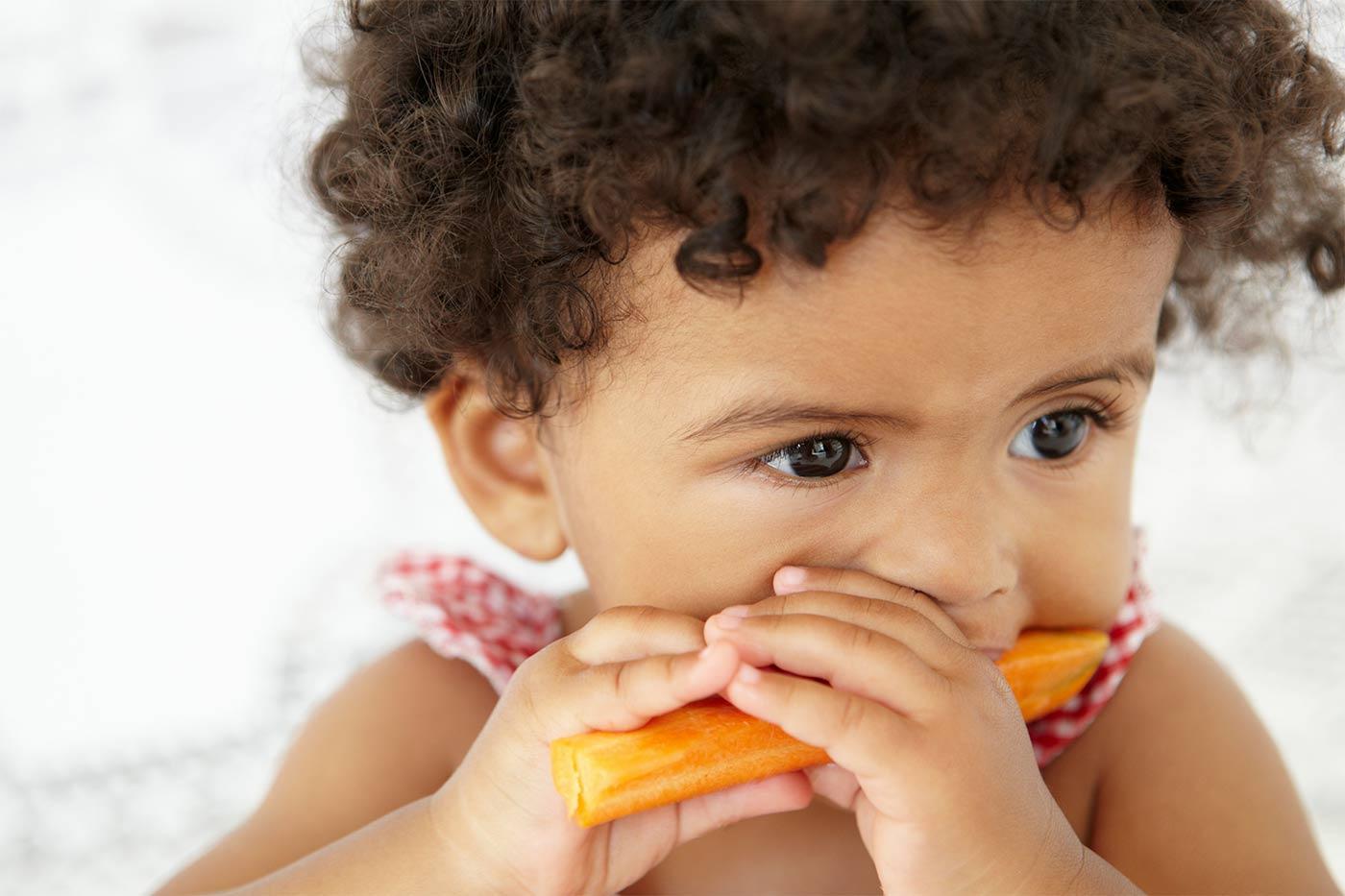 Little girl eating a carrot