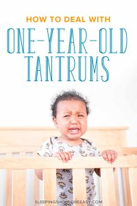 1 year old boy throwing a tantrum and crying, standing in a crib with hands on the railing