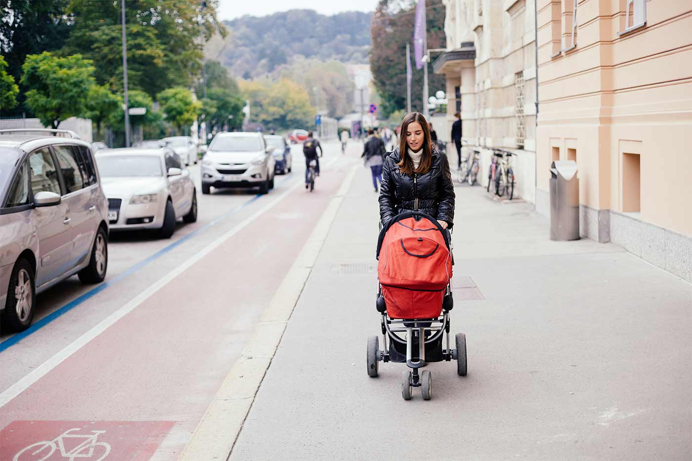 Mom pushing a stroller on a sidewalk