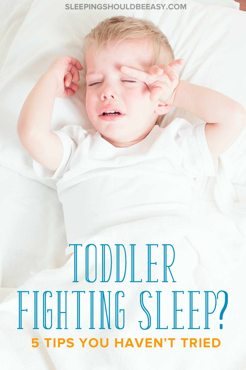 Toddler fighting sleep in his bed, crying