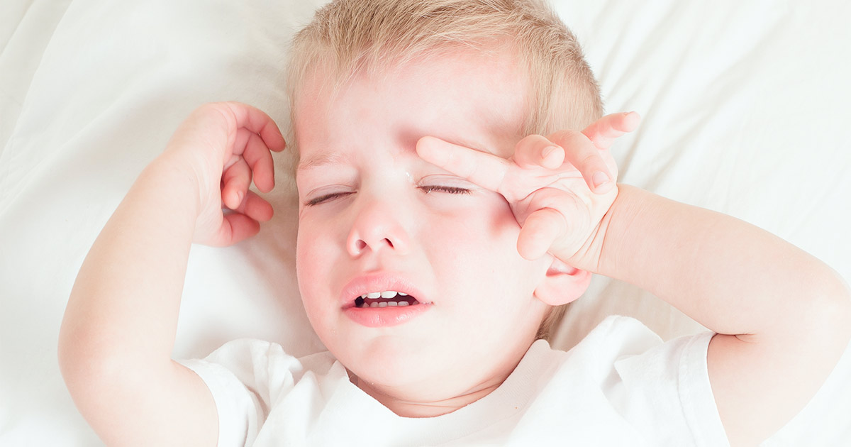 Toddler boy crying in bed