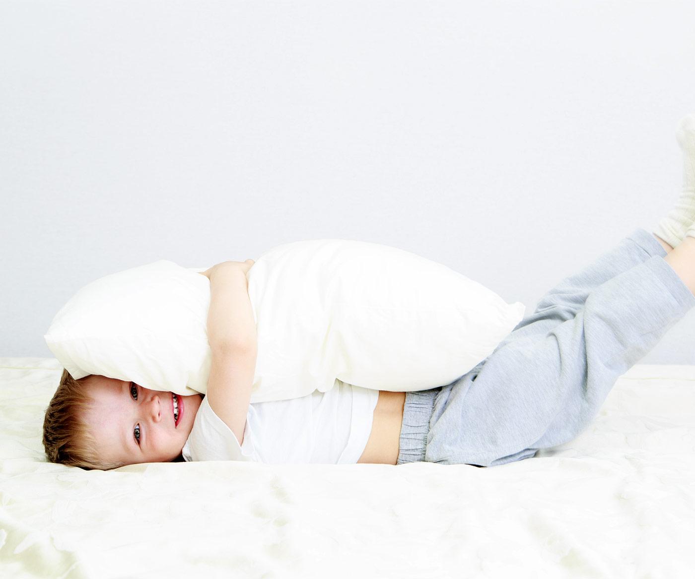 Little toddler hugging a pillow