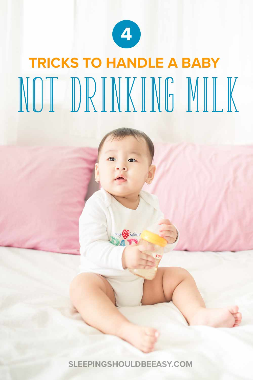 A baby not drinking milk, holding a milk bottle