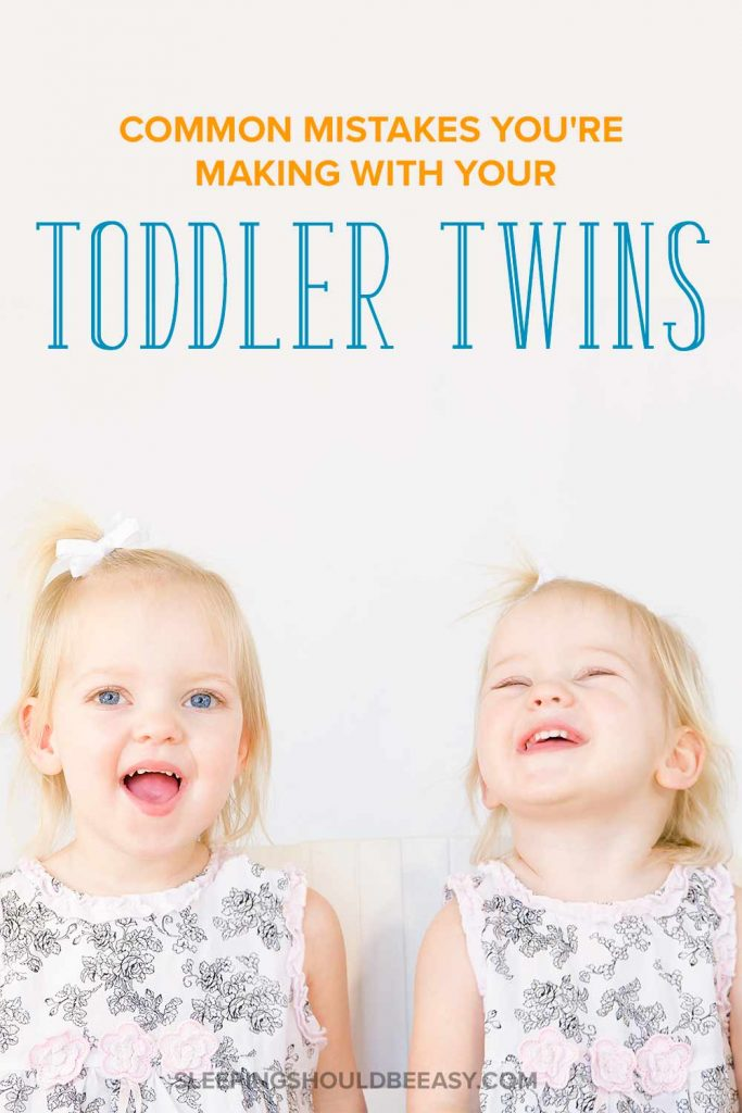 A pair of toddler twins smiling