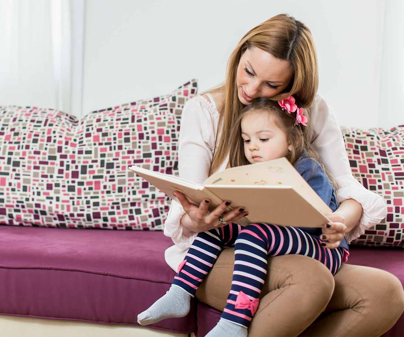 mom and girl reading on a couch