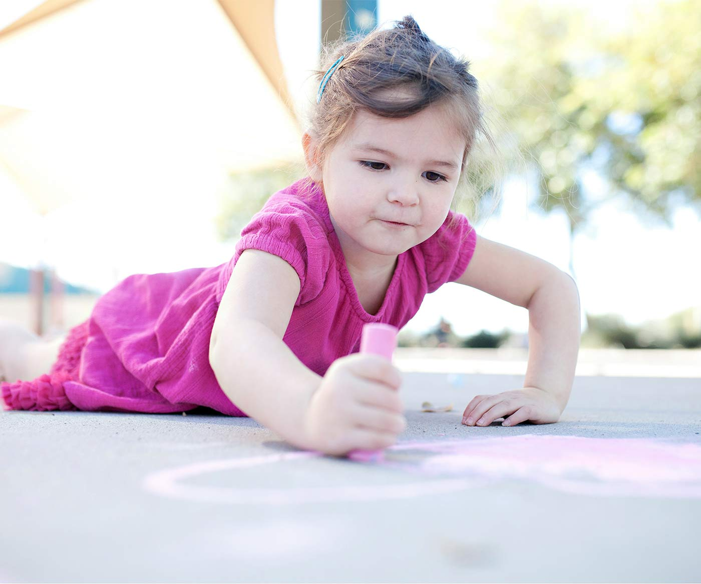 An independent toddler drawing on chalk