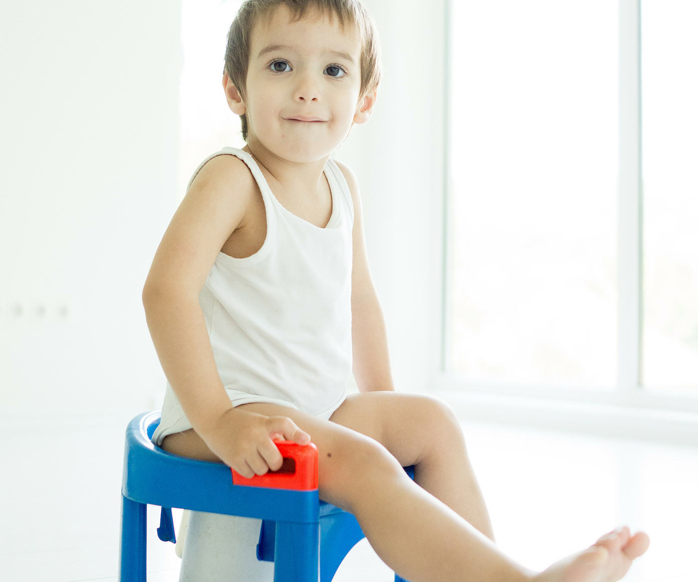 How to potty train in 3 days: Little boy sitting on a potty