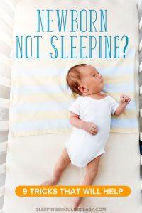 Little newborn not sleeping, lying in a crib