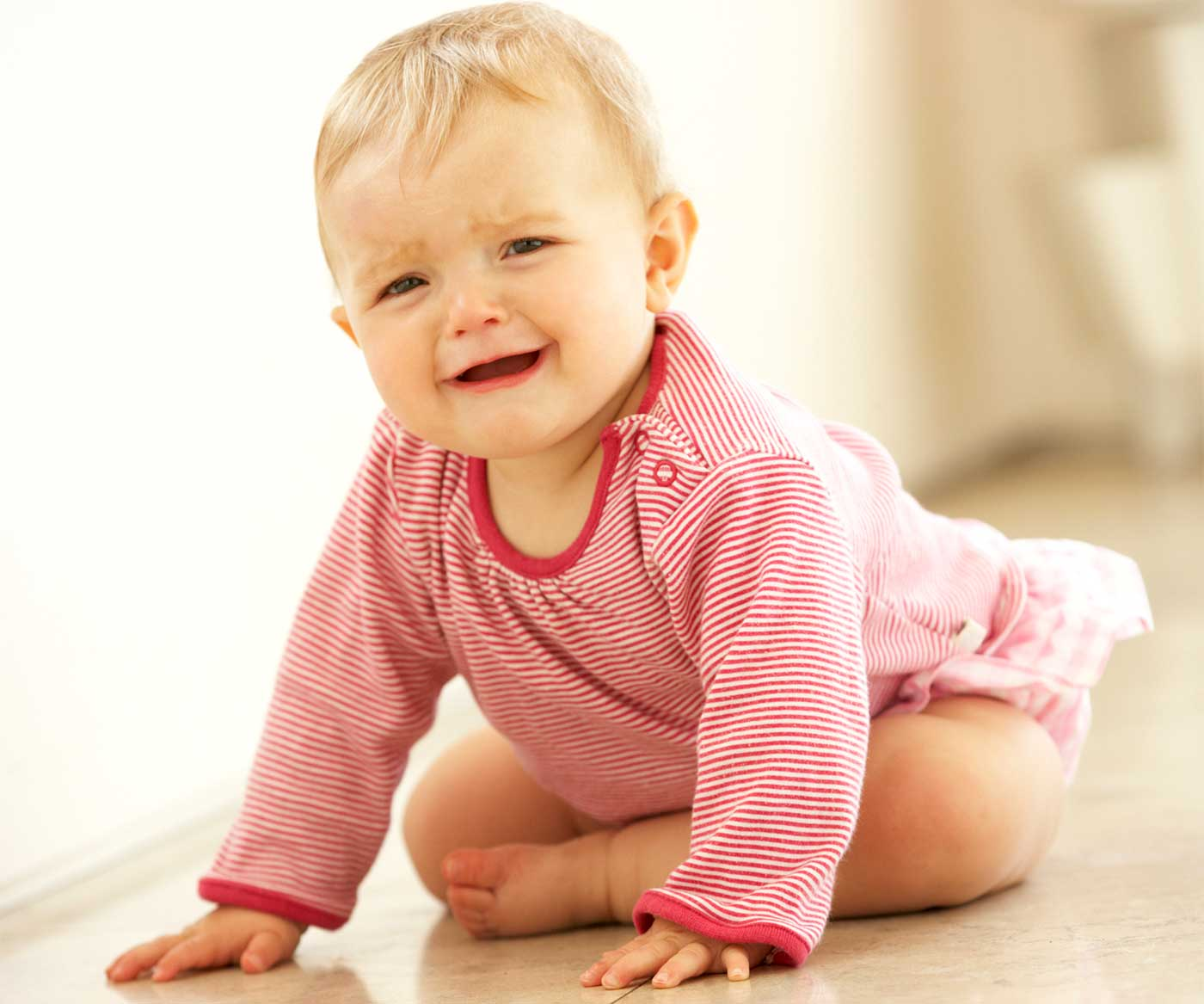 baby crying and sitting on the floor: separation anxiety in babies