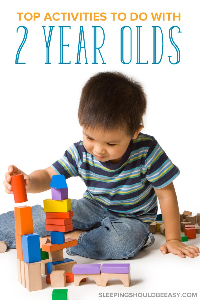 A little boy playing with blocks, participating in activities to do with 2 year olds
