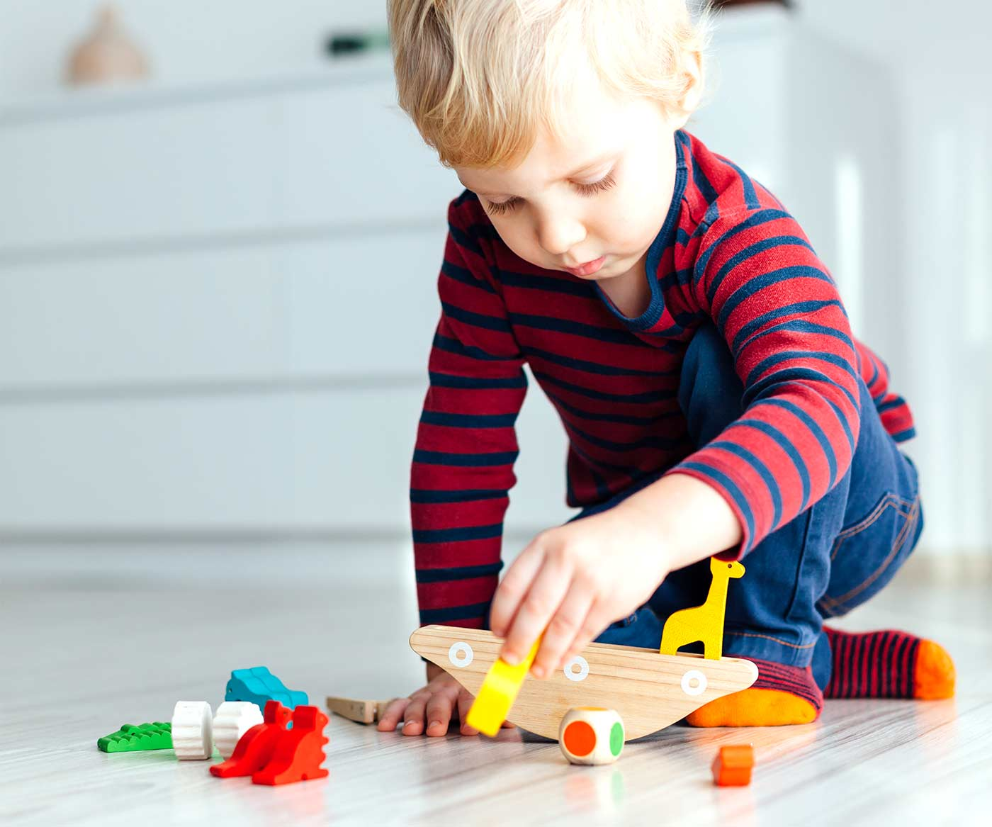 Little boy playing with toys: why you should rotate toys