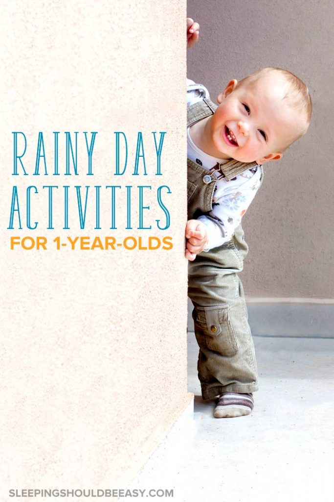 A little boy hiding behind a wall, smiling, during rainy day activities for 1 year olds