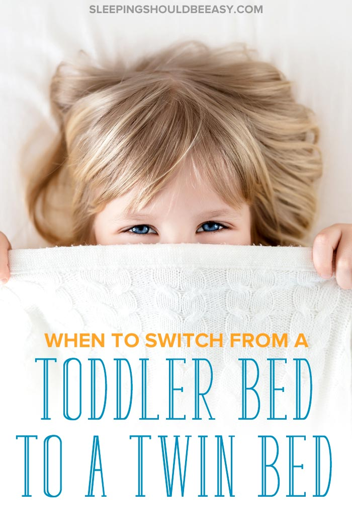 Little girl peeking from under a blanket: when to transition from toddler bed to twin bed