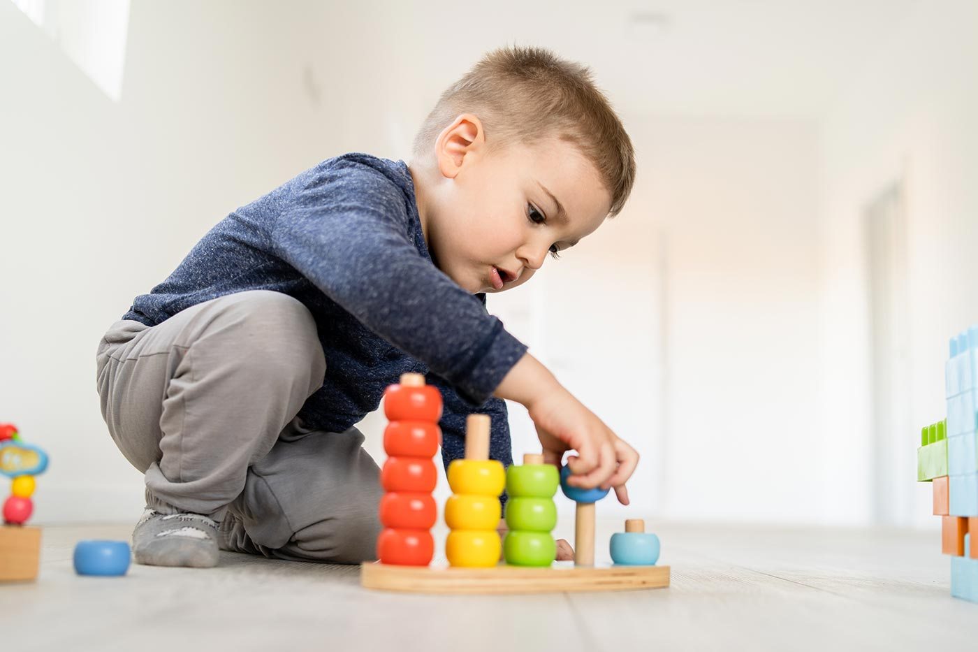 Small boy playing with little wood toys at home