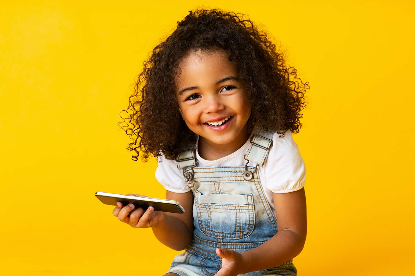 Girl holding cellphone and smiling
