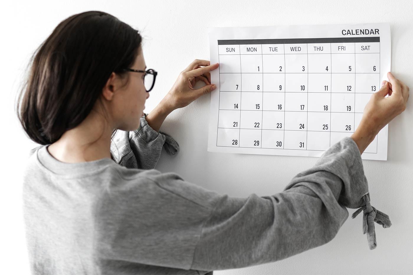 woman hanging a calendar