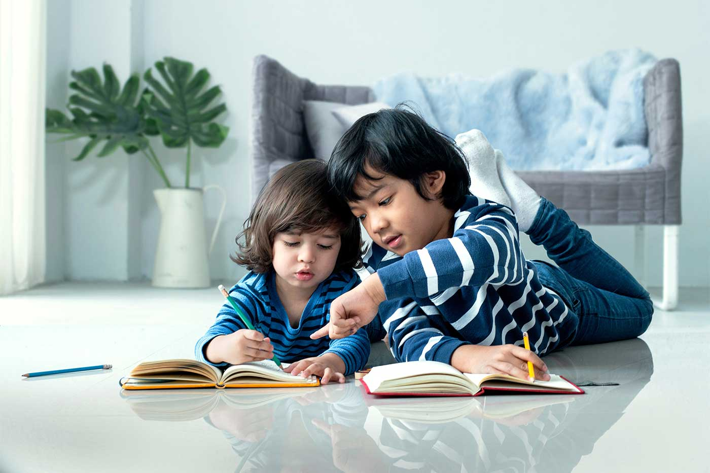 Older brother teaching his brother how to do homework