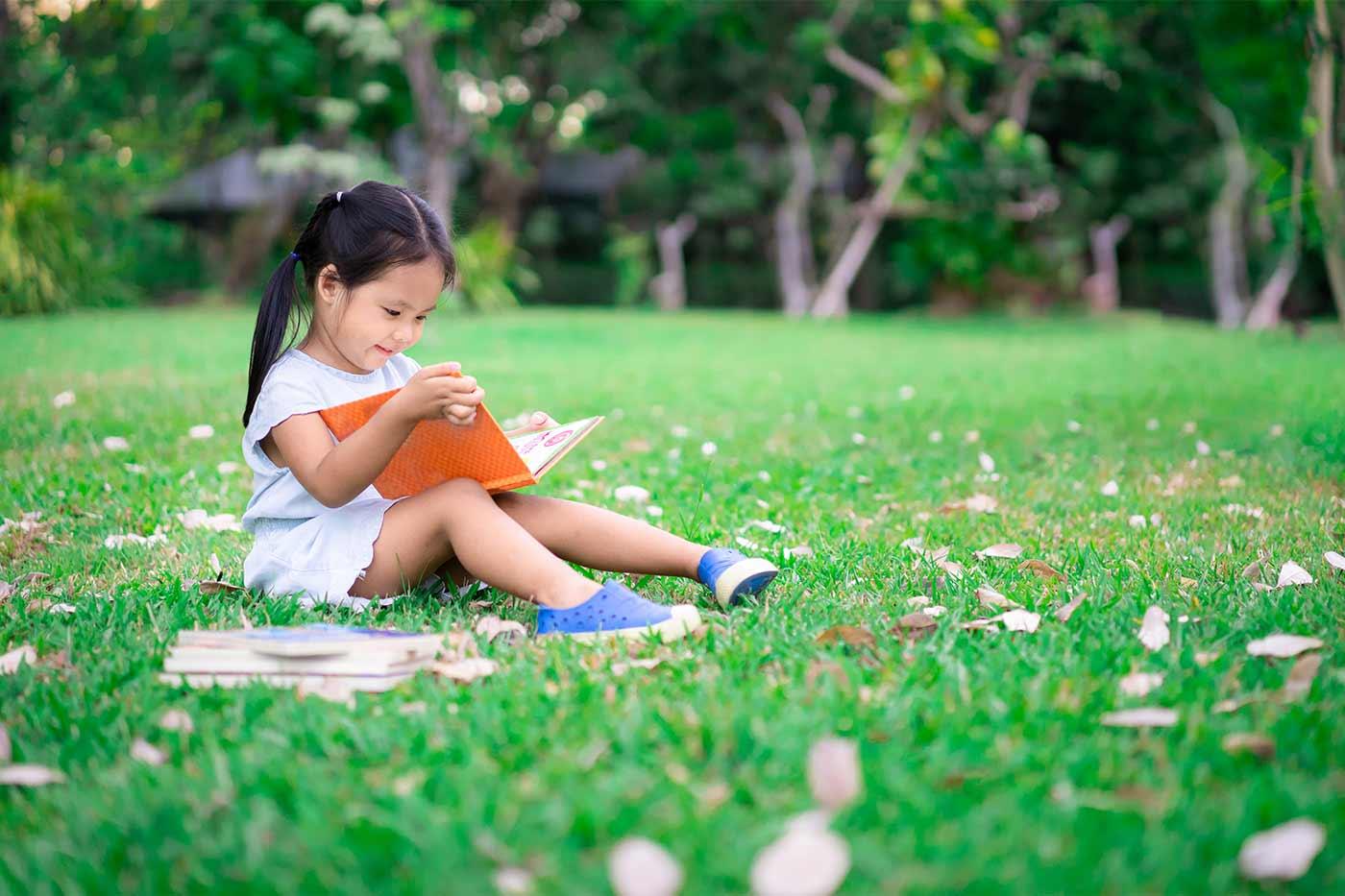 a little girl reading a book outdoors