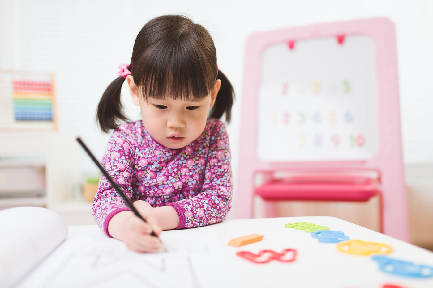 Toddler girl practicing writing letters
