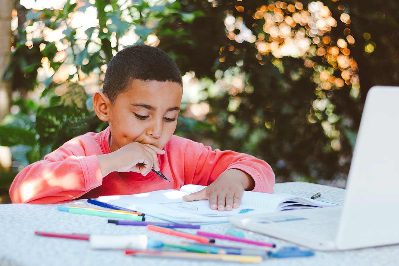 boy doing homework outside