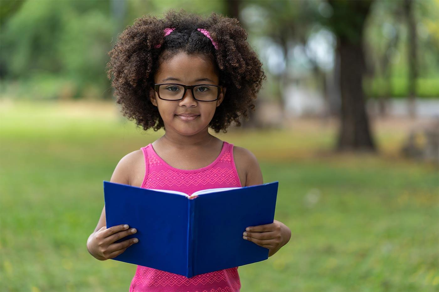 little girl reading a book outdoors