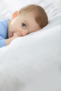 8-month-old baby boy laying on bed