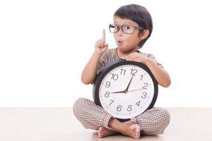 早起きする方法のコツを教える目覚まし時計を持った子どもの画像
