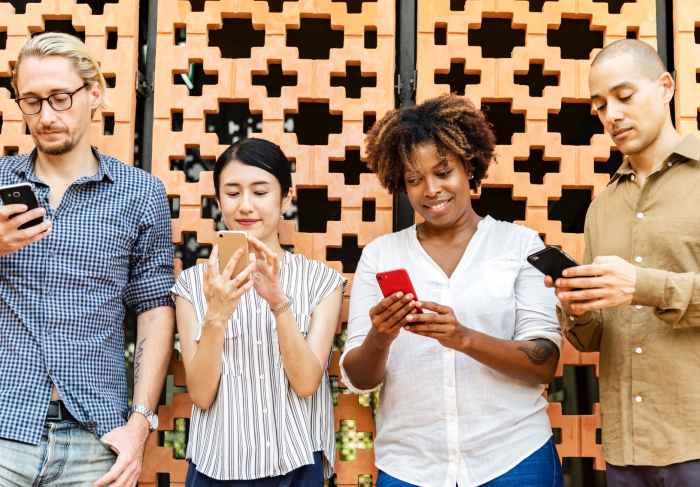 four people holding mobile phones