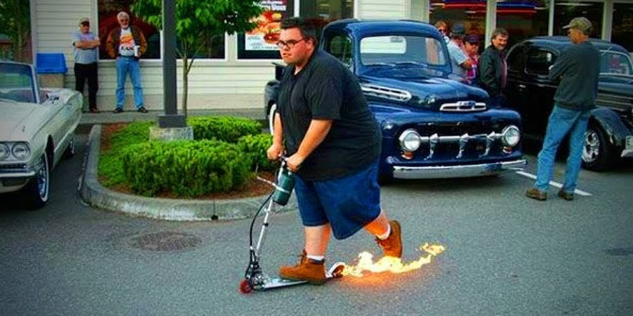 Overweight man riding e-scooter with flames shooting out the back