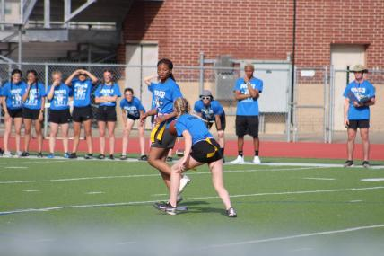 Dani Bautista pitches the ball to Jada Lake. Jada was a force on the blue team and helped gain many of their yards.
