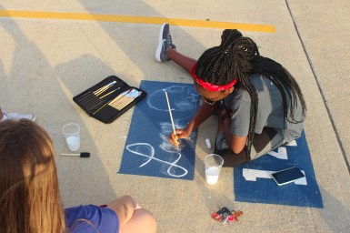 Outlining her rough sketch, senior Kendal Lacy paints precise brush strokes over her chalk lines. She painted her first name with a pair of headphones, displaying her love of music.