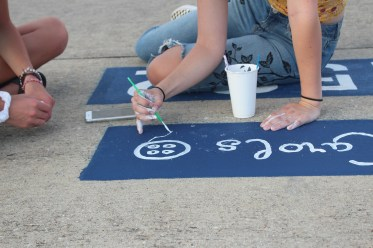 Helping out her friend, senior Bri Johnston paints a button on senior Caroline Canterbury's parking spot. Canterbury wanted to paint a Coraline themed parking spot piece because Caroline reminded her of Coraline.