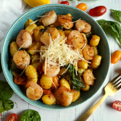 Blue bowl filled with gnocchi, shrimp, and vegetables.