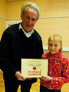 Johnny Rigney presents Deirbhile C Fennell with a Certficate of Creative Participation for her Garland of eggshells for the May Bush in Rosenallis - photo Kathleen Culliton