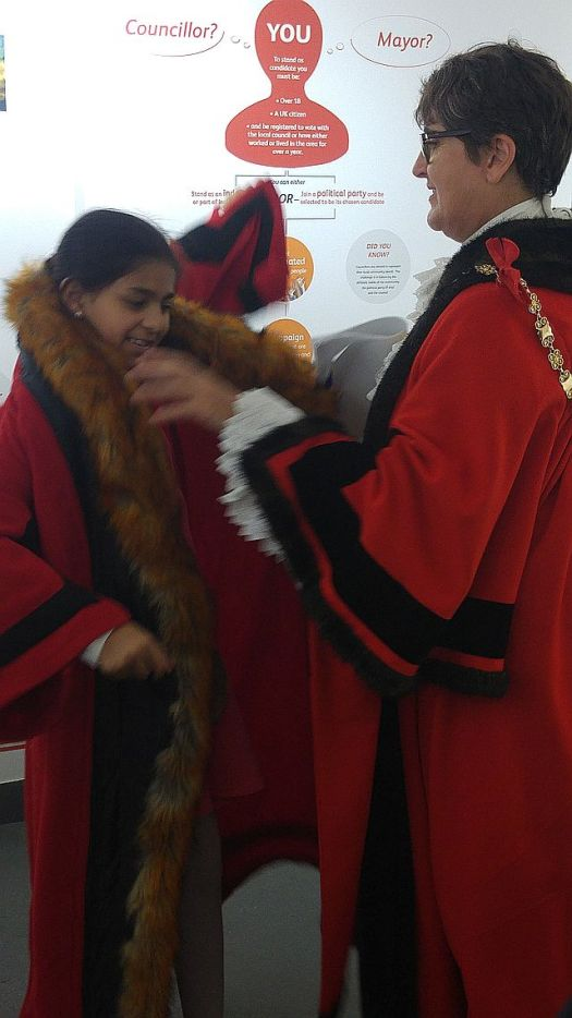 Carol Potter, the Speaker, helping a young visitor dress as the mayor