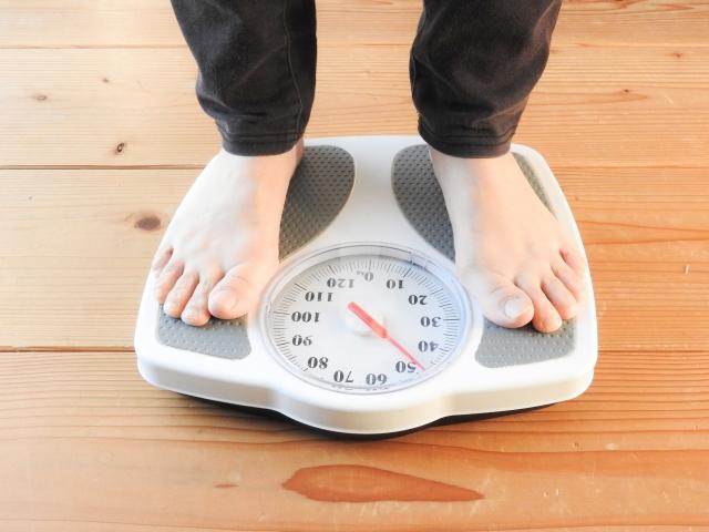 ダイエット成功して体重計に乗る女性