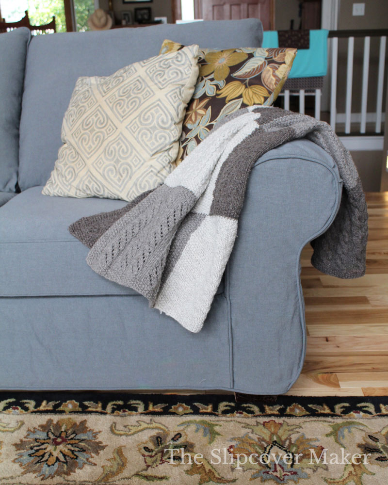 Grey Sofa with patchwork blanket and throw pillows.